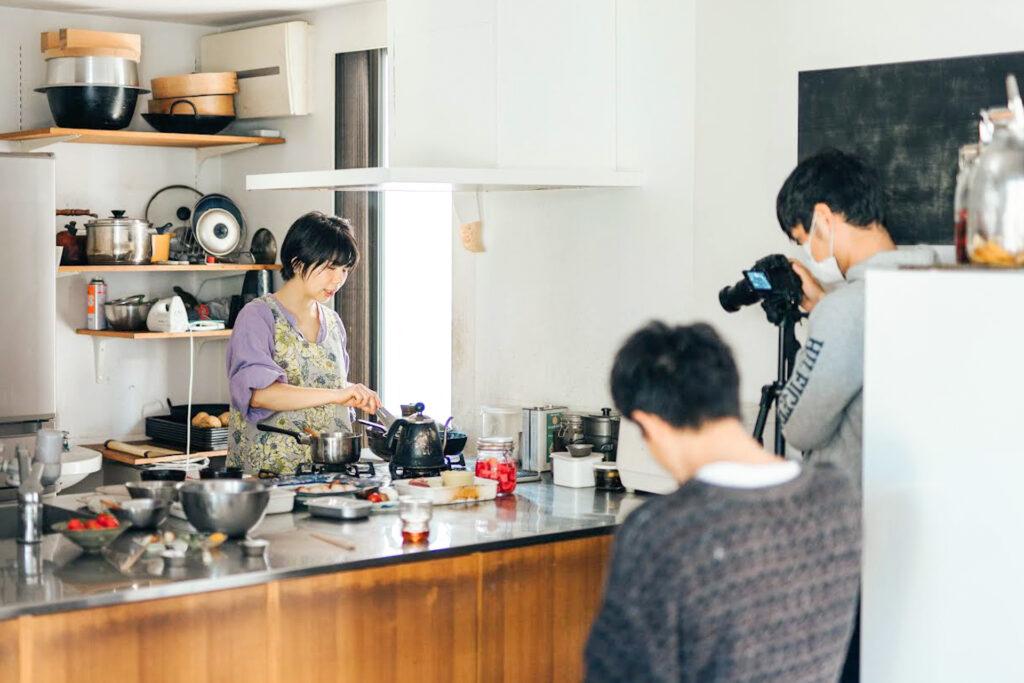 オープンキッチンで料理する女性